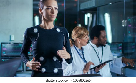 Woman Athlete Runs on a Treadmill  with Electrodes Attached to Her Body while Two Scientists Supervise whole Process. In the Background Laboratory with Monitors Showing EKG Readings.