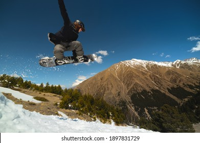 Woman athlete snowboarder flies after jumping from kicker doing trick