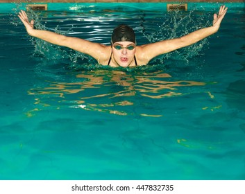 Woman athlete swimming performing butterfly style stroke in pool. Active human swimmer taking breath. Water sport comptetition.