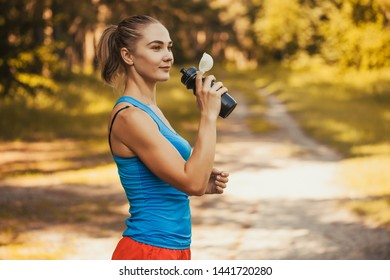 woman athlete takes a break, she drinking water, out on a run on a hot day. Sport concept