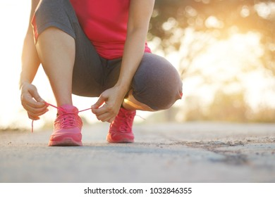 Woman athlete tying running shoes on rural street at sunset background. Sport lifestyle.