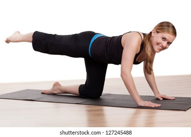 Woman athlete working out practicing body and muscle control as she kneels on a gym mat raising her leg backwards in the air in a health and fitness concept