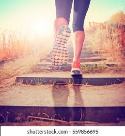 femme avec une paire de jambes athlétiques allant faire un jogging ou courir au lever du soleil ou au coucher du soleil, monter des escaliers dans les montagnes, concept de style de vie sain toné d'un filtre instagram rétro vintage ou effet action