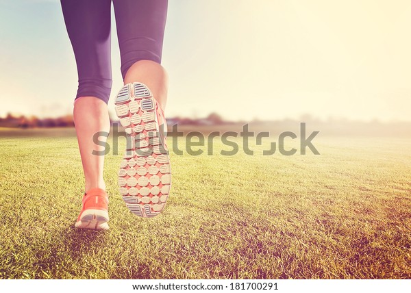 a woman with an athletic pair of legs going for a jog or run on grass during sunrise or sunset - healthy lifestyle concept done with an instagram like filter