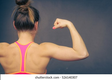 Woman athletic young girl showing muscles of the back and shoulders on black background. Beauty fit female body