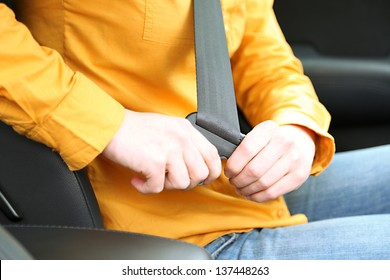 Woman attaching seat belt in the car, close up