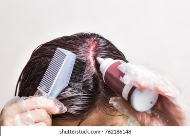 Woman attempting to apply chemical hair color onto scalp.  Self help solution.