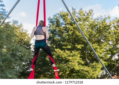 Woman is attempting a split on red ribbon