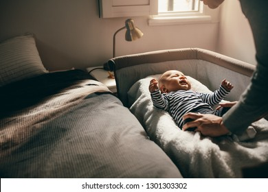 Woman attending to her crying baby trying to pacify him. Mother putting her baby to sleep in his bassinet.