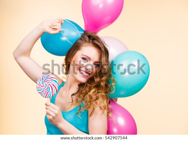 Woman attractive cheerful girl holding colorful balloons and sweet lollipop in hands. Summer holidays, celebration and happiness concept. Studio shot bright yellow background