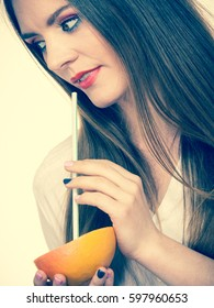 Woman attractive long hair girl eyes makeup holding grapefruit citrus sipping juice from fruit. Healthy diet food. Summer vacation holidays concept. Toned image