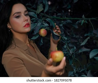 woman in autumn dress is standing under apple tree and looking at a red apple. Red and green apple in female hand.