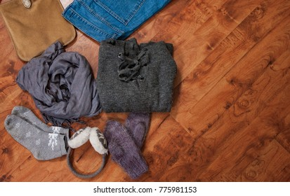 woman autumn and winter clothes collage set on wooden floor, flat lay, top view