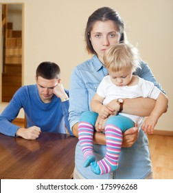 Woman with baby against husband after quarrel at home