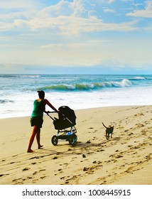 Woman with a baby carriage and a dog walking by the beach. Bali island, Indonesia
