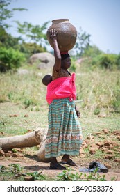 A woman with baby carrying container on her head for collecting water in Uganda -Africa on 12 April 2017