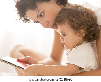 Woman and baby girl Reading. Mother and her little baby girl on bed.
