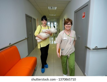 Woman with a baby on hands walking in a corridor of a maternity hospital, nurse leading her. City perinatal center. April 12, 2019. Kiev, Ukraine