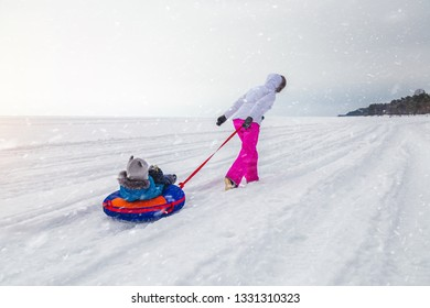 woman with a baby on the tubing in winter
