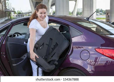 Woman with baby safety seat placing it in the car
