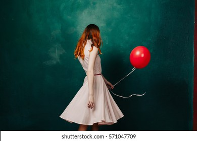 A woman from the back with an air balloon flying in the hands of.
