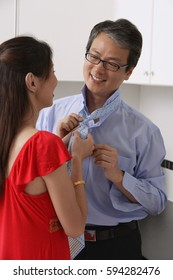 Woman with back to camera tying man's tie, looking at each other, smiling