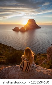 Woman back to the front watching a beautiful sunset at the beach. The beach is called Es Vedra, in Ibiza and belongs to balearic islands, in Spain