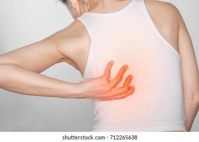 woman with back pain. Female holding hand to spot of back. Concept photo with read spot indicating location of the pain.