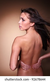 Woman with back pain holding lower back