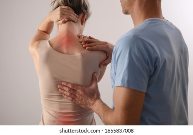 Woman with back pain. Spine physical therapist and patient. Chiropractic pain relief therapy.