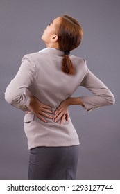 woman with back pain symptoms, office syndrome; portrait of asian woman suffering from back pain injury, girl with slipped backbone disc or herniated spinal disc injury; asian adult woman model