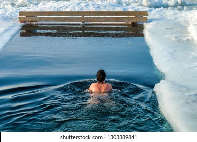 A woman from the back is swimming in icy water. Extreme water sport. Ice hole swimming. Winter vacation. Winter, very cold, blue water, ice around the edges