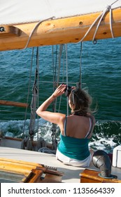 Woman with back turned taking pictures while on wooden schooner sailboat.