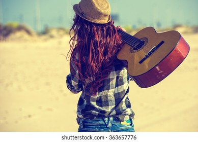 Woman back walking on the beach with guitar