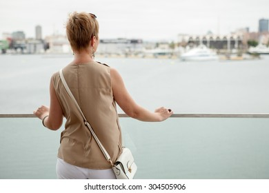 Woman back watching the boats in the harbor