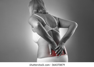 Woman with backache. Pain in the human body on a gray background. Black and white photo with red dot