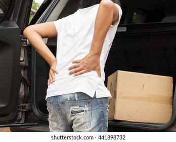 Woman with backache while lifting box in the car.