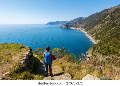 Woman with backpack admiring the view in Cinque Terre, Italy
