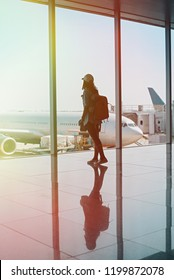 woman and backpack in hall airplane departure.Traveler woman plan and backpack see the airplane at the airport glass window.Travel Concept