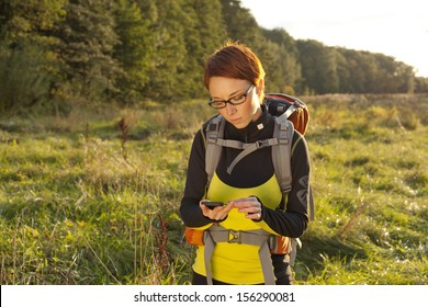 Woman with backpack looking to compass and searching the way / geocaching