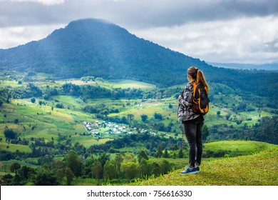 Woman with backpack on mountaintop at Khao Ta-Khian Ngo Viewpoint. The location in Khao Kho District, Phetchabun, Thailand, Southeast Asia.