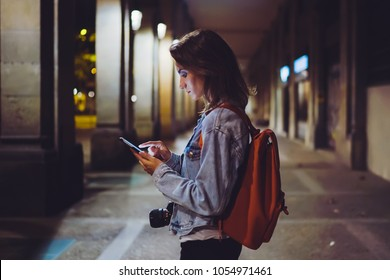 Woman with backpack pointing finger on blank screen smartphone on background in night atmospheric city, blogger hipster using in hands gadget mobile phone, mockup street, online wifi internet concept