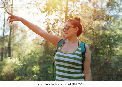 Woman with backpack pointing out in forest at sunset