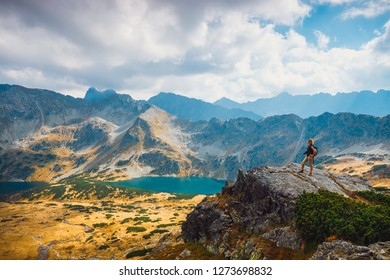 woman with backpack standing on top of a mountain and enjoying beautiful view