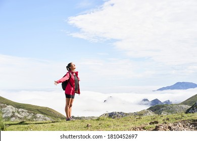 Woman with backpack standing and with open arms on top of a mountain and looking somewhere. He wears a red jacket. In the background you can see mountains surrounded by mist.