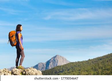 山の上にバックパックを背負った女性が立ち、山の谷の美しさに憧れ、美しい場所に旅をし、ゴールに着く。 美しい風景。