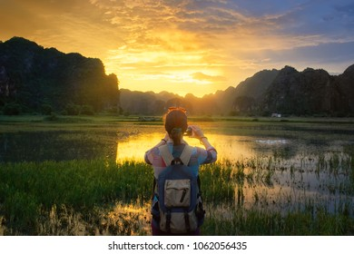 Woman with backpack travels and photographs a beautiful sunset over the mountains in the countryside in Vietnam.Travel and discovery, happiness emotion, summer holiday concept