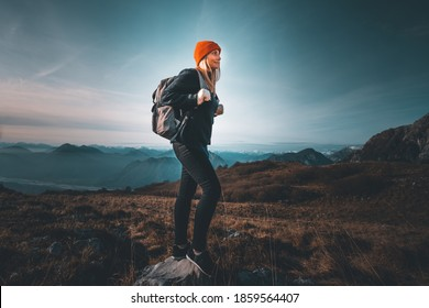 Woman with backpack and winter cloths hiking in the mountains