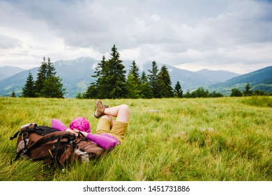 woman backpacker enjoy the view on green summer mountains