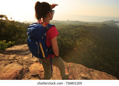woman backpacker enjoy the view sit on top of mountain